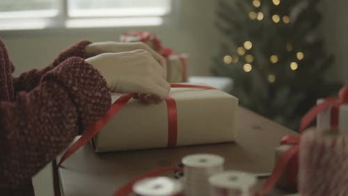 Woman Binds Bow On Gift