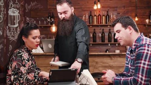 Couple Ordering To a Bearded Waiter