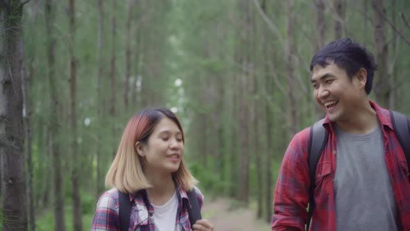 Asian backpacker couple on hiking adventure freedom walking in forest, holidays near lots of tree.