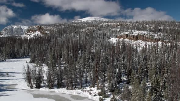 Flying backwards above frozen lake past trees