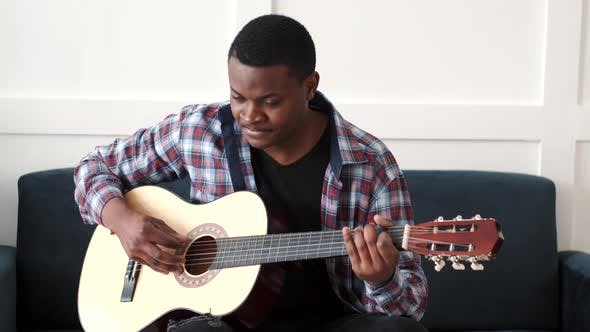 Young African Man at Home Playing Guitar