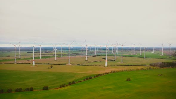 Thumbnail for Drone Slowly Flying Away From Windmill Turbine Farm in Cloudy Autumn Field, Ecological Renewable