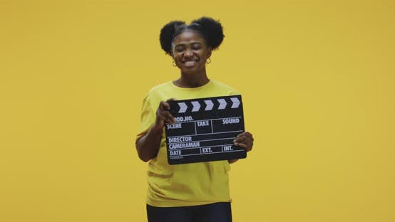 Thumbnail for Cheerful Woman Clapping Clapperboard
