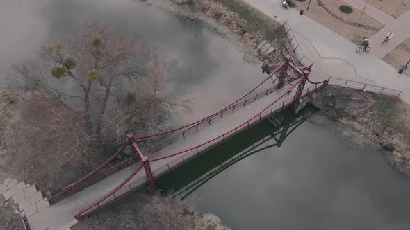 Thumbnail for Woman runs on bridge across river in recreation area with park and quay.
