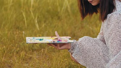 Young Woman Picking Up Colors the Palette