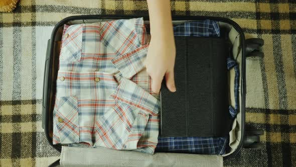 Thumbnail for Mom Puts Things in a Suitcase. The Child Also Puts His Toy There. Travel with Children Concept