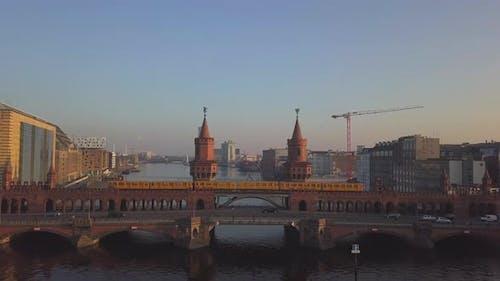 AERIAL: Berlin Yellow Subway Crossing Bridge, Oberbaumbruecke in Blue Sky Over Spree Close Up