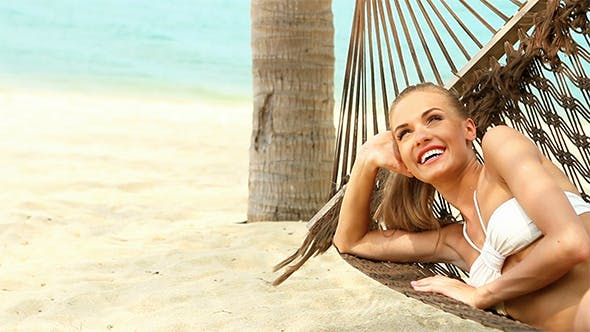 Thumbnail for Happy Young Woman Relaxing In A Hammock
