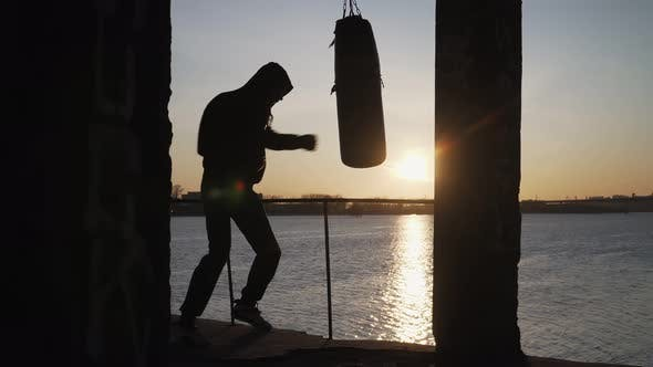 Thumbnail for Silhouette Boxer Against the Backdrop Beautiful Sunset and River, Trains Blows on Punching Bag.