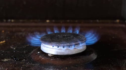 Dirty old gas stove. The burner on the stove burns with a blue flame