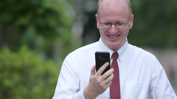 Thumbnail for Happy Mature Bald Businessman Using Phone Outdoors