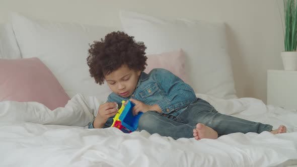 Thumbnail for Serious Cute Little Kid Repairing Toy Car on Bed