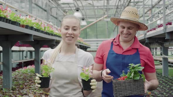 Thumbnail for Male and Female Biologists Walking in Greenhouse with Flowers and Chatting. Portrait of Positive