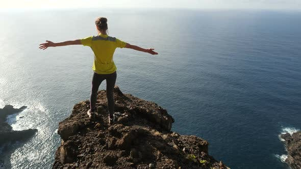 Thumbnail for Young Woman Raising Her Arms on Beautiful Steep Cliff Over the Ocean