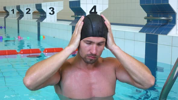 Thumbnail for A Professional Swimmer Puts on a Cap and Goggles and Smiles at the Camera in an Indoor Pool