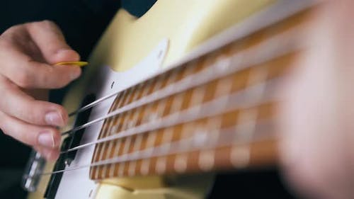 Delighted Bassist Plays White Guitar with Yellow Pick