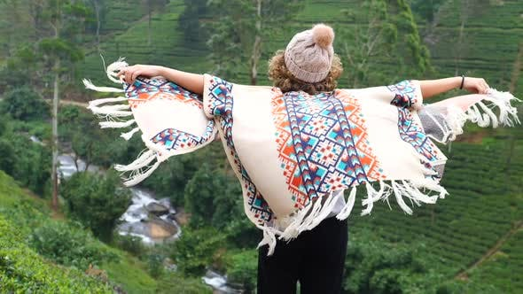 Thumbnail for Inspirational Uplifting Woman In Poncho Spreading Arms Facing Green Hills