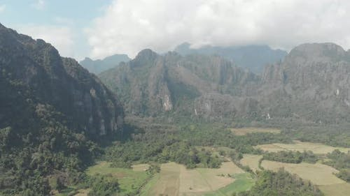 Aerial: flying over scenic cliffs rock pinnacles tropical jungle rice paddies