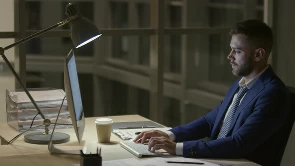 Cover Image for Businessman Texting on Computer at Night