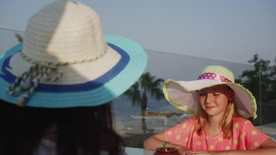 Smiling Teenager Girl in Summer Hat Talking in Outdoor Cafe with Sea Beach View