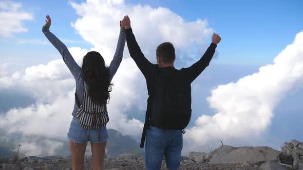 Thumbnail for Young Couple of Tourists with Backpacks Reaching Up Top of Mountain and Raised Hands. Man and Woman