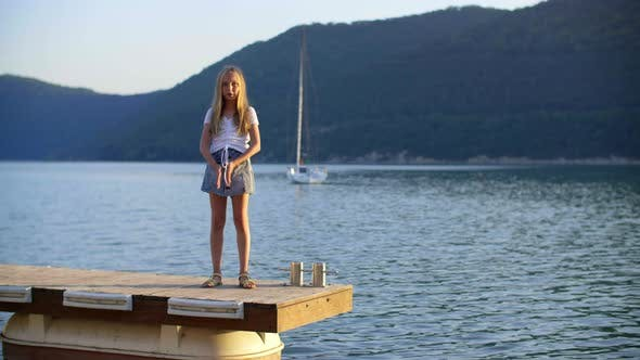 Thumbnail for Happy Girl Teenager Dancing on Pier on Green Hills and Yacht Landscape. Cheerful Young Girl Dancing