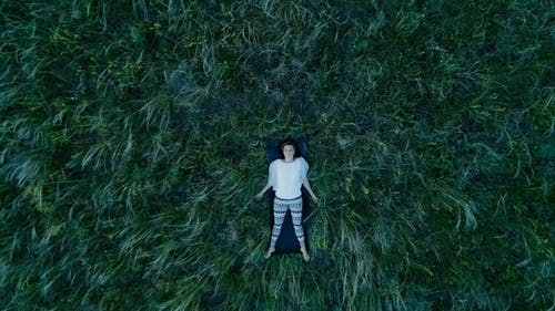 Girl lies in the grass and meditates