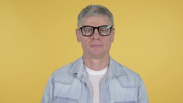 Cover Image for Casual Senior Man Looking at Camera on Yellow Background