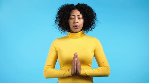Calm African Woman Praying with Hands Together Symbolizing Prayer and Gratitude