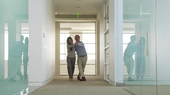 Thumbnail for Businessman and Businesswoman dancing down hallway
