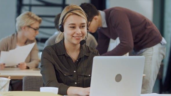 Thumbnail for Smiling female helpline operator with headphones at her
