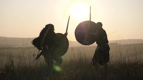 Mittelalterliche Krieger kämpfen bei Sonnenuntergang