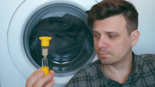 Man with Sandglass is Waiting the Washing Machine with Grey Bedspread Inside It