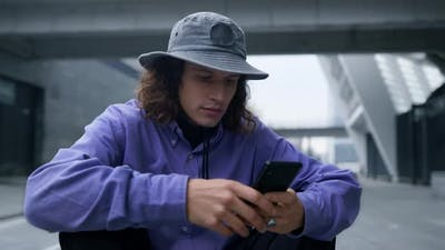 Focused Hipster Using Cellphone Outdoor