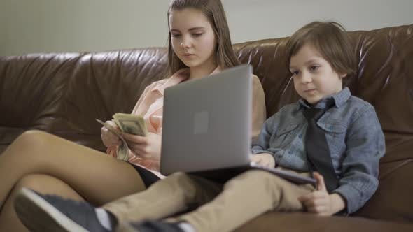 Cover Image for Portrait Older Sister and Younger Little Brother Sitting on the Leather Sofa. The Boy Holding Laptop
