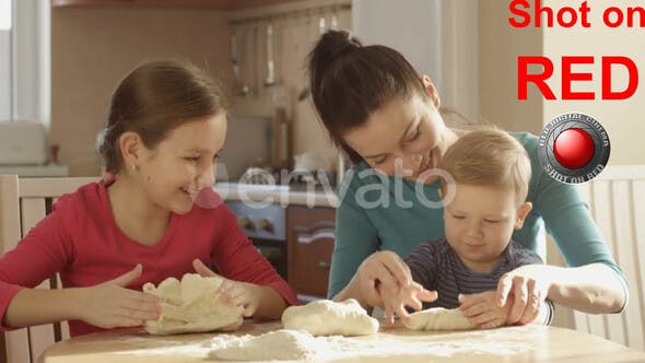 Thumbnail for Happy Family Cooking Mother With Children Kneading Dough For Cupcake In The Kitchen At The Table