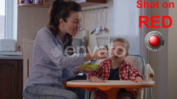Cover Image for Portrait of Happy Family with Child Sitting In A Baby Chair And Eating Food With Mother