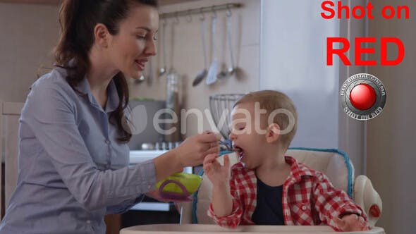 Thumbnail for Portrait of Happy Child Enjoying Eating Food With Happy Mother Sitting In A Baby Chair