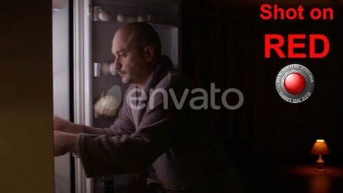 Hungry Man Eating Food At Night Opening Refrigerator