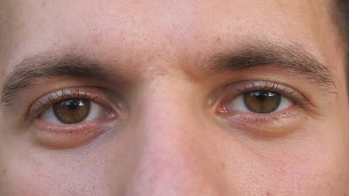 Detail View Brown Eyes of Guy Staring and Blinking with a Tired Sight