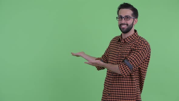Thumbnail for Happy Young Bearded Persian Hipster Man Talking While Showing To Back