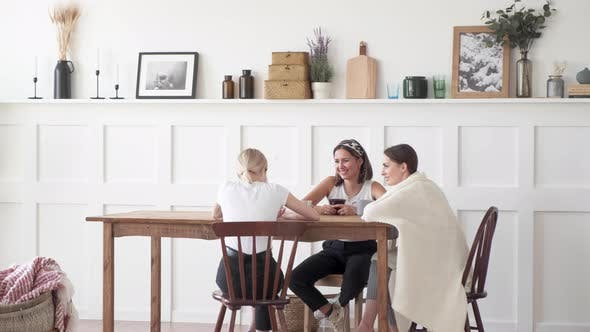 Thumbnail for Three girls sit at a table and on chairs in a large room at home and talk, telling stories