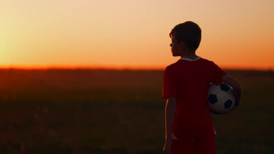 Thumbnail for The Camera Follows the Boy Walking at Sunset in the Field with the Ball.