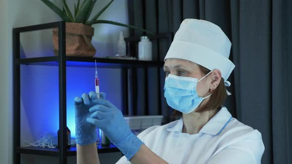Doctor scientist is carefully preparing syringe for injection with preventive medication for COVID
