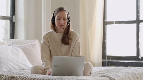Thumbnail for Smiling Woman Wearing Headset Looking at Laptop Sitting on Her Bed with Laptop Making Video Call