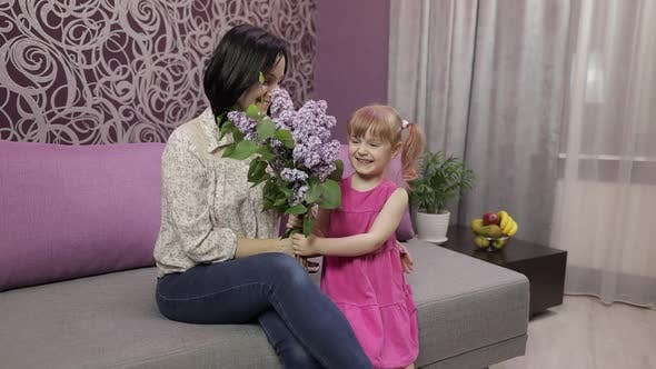 Thumbnail for Little Daughter Child Congratulates Mother with Bouquet of Flowers. Slow Motion