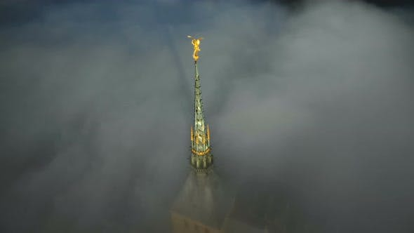 Thumbnail for Atmospheric Aerial Close-up Shot of Glowing Golden Statue on Top of Mont Saint Michel Castle Steeple