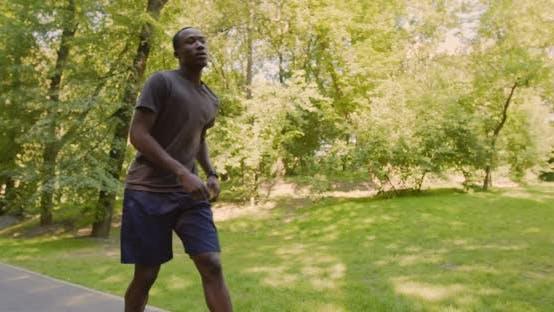 Thumbnail for Erschöpfter Afroamerikaner stoppt während des Laufs zum Atmen, dann weiter Joggen im Park