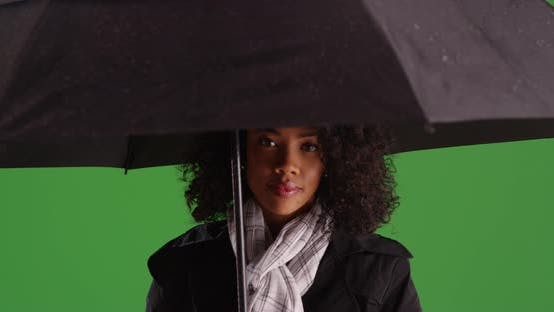 Thumbnail for Beautiful African-American woman in raincoat under black umbrella on greenscreen