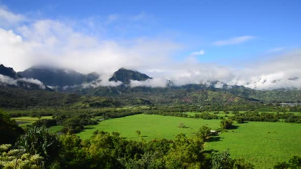 Kauai sunny day green land and cloudy mountains view